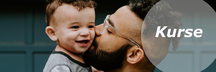 Link zu den Hebammen-Kursen: Ein Mann mit Vollbart und Undercut küsst sein Baby